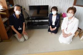 小学生の居間の贈呈品ブルーレイレコーダーの前で岩井館長・竹本会長・垪和副会長