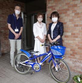 善隣館玄関前で自転車の贈呈品前で岩井館長・竹本会長・垪和副会長